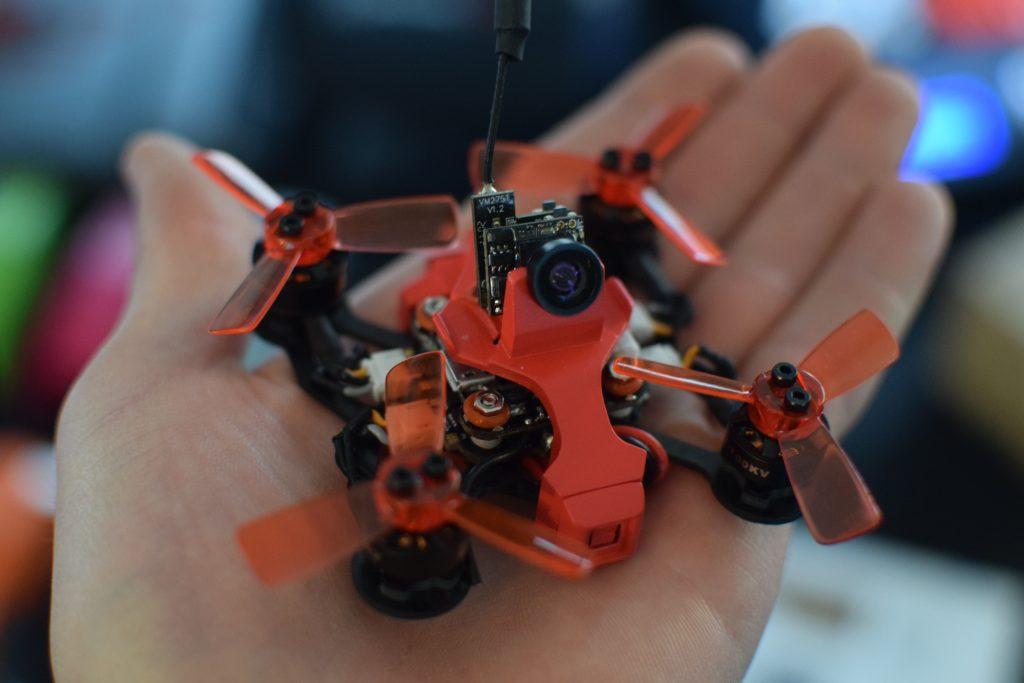 Drone, CES, Drone Rodeo. A bright orange drone sits in the palm of a pilot's hand.