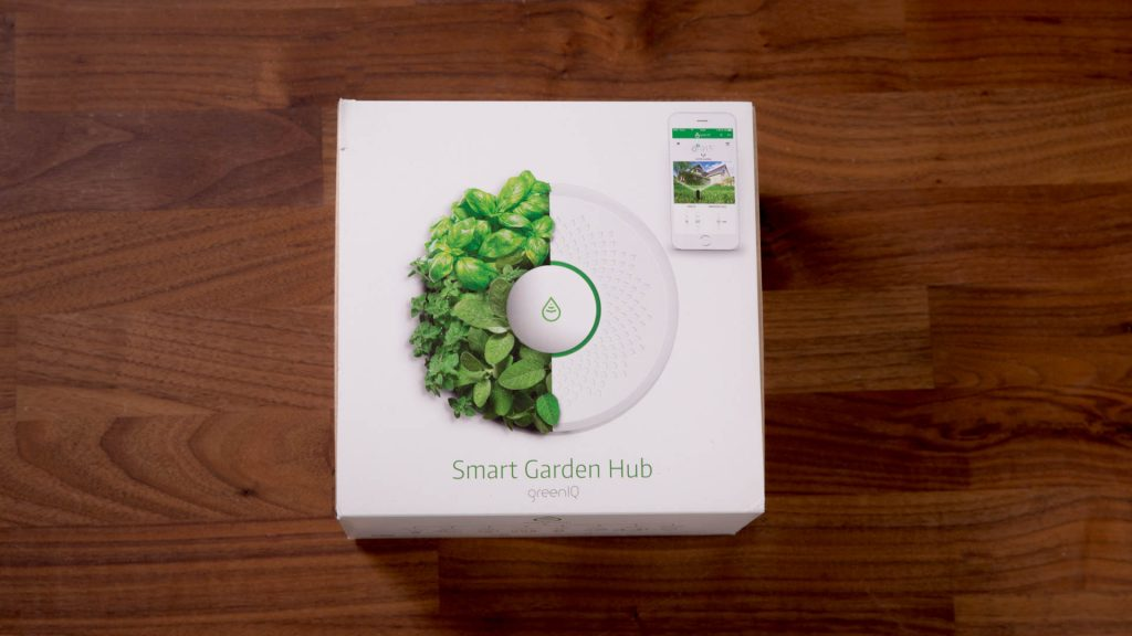 Smart Home, outdoor tech, smart irrigation controller, GreenIQ, the white and green GreenIQ box on a wooden table