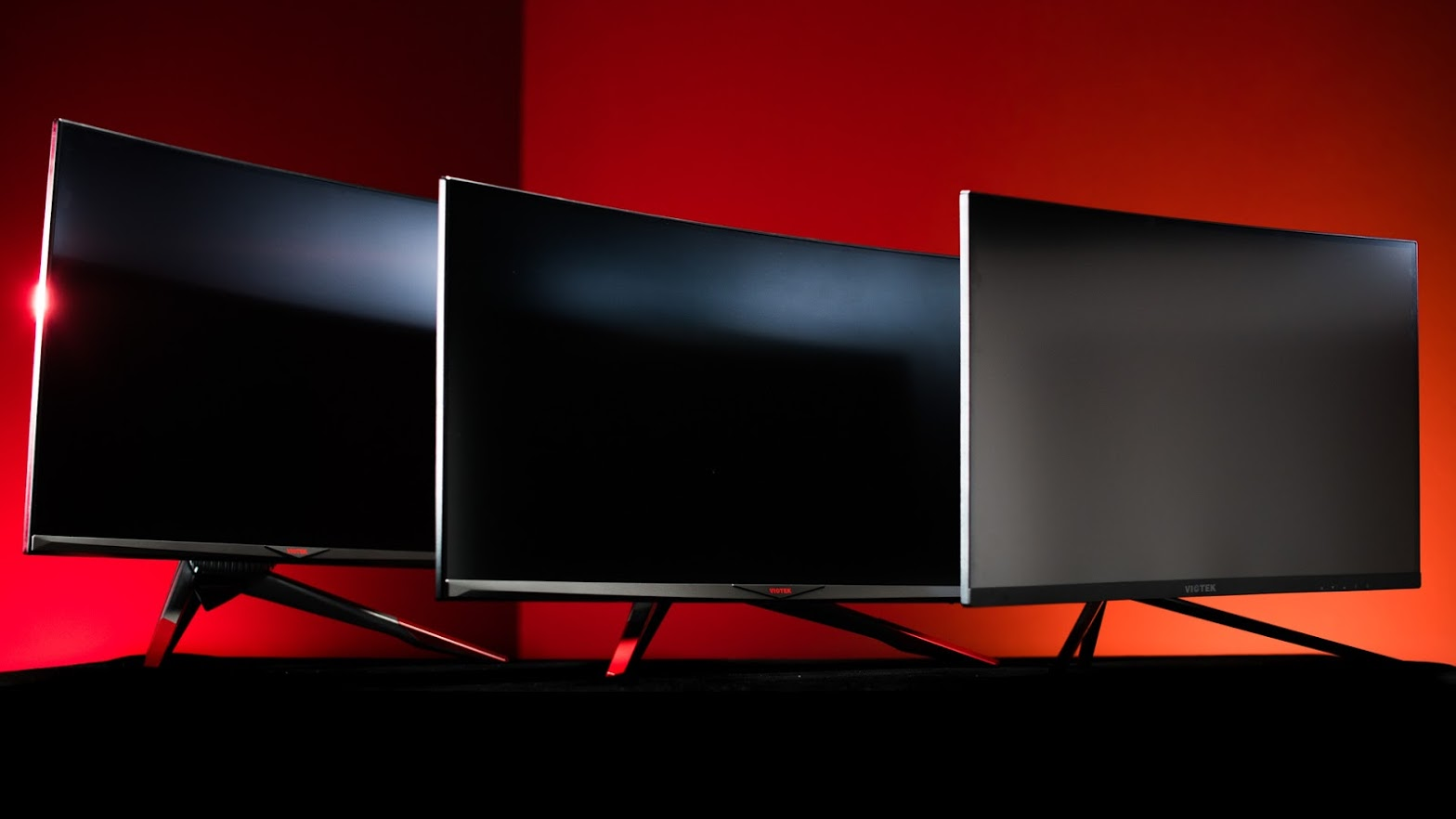 Three Viotek Gaming Monitors in different sizes, angled to the right, behind one another