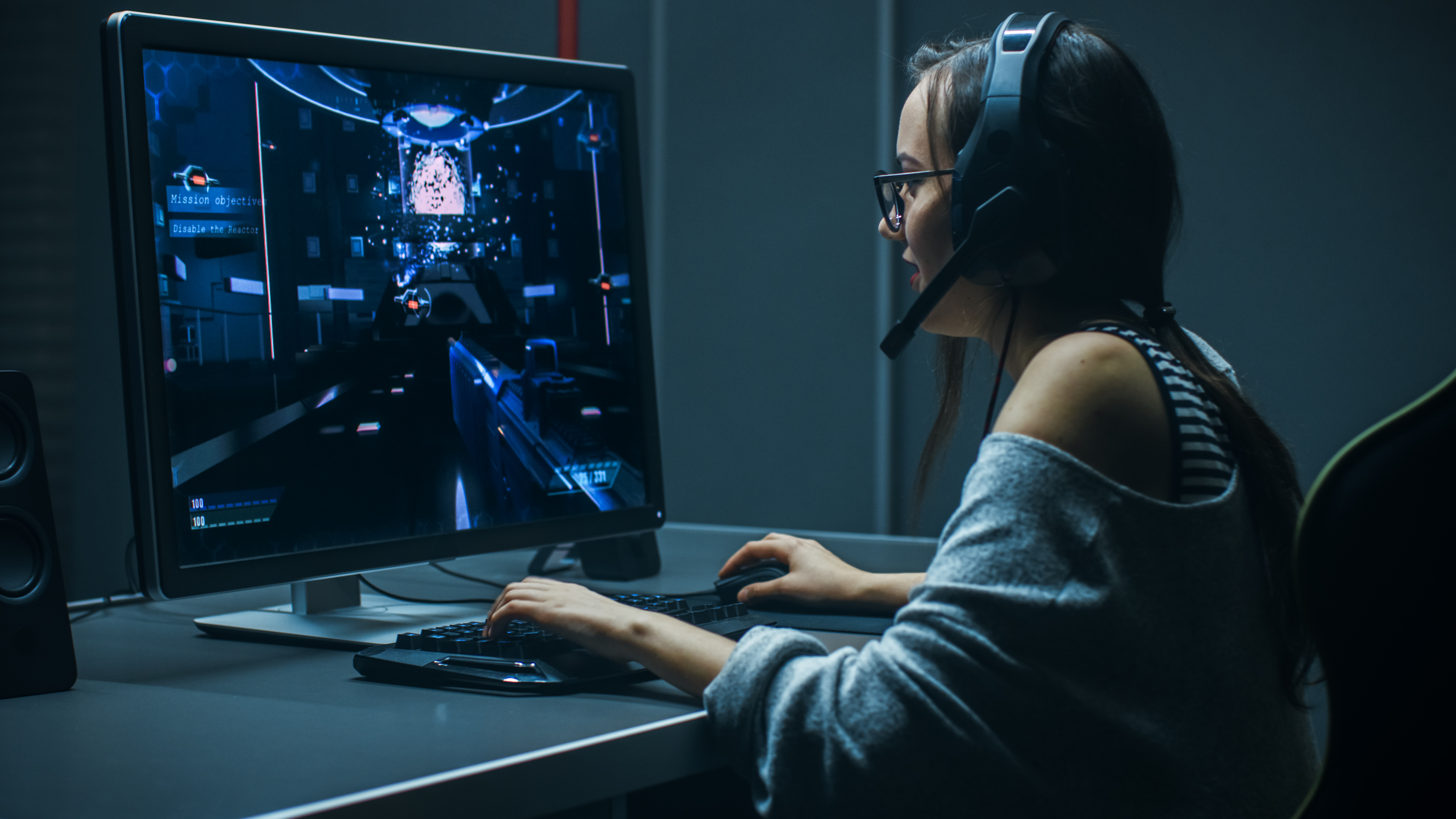 Female gamer playing on a large computer monitor with keyboard, mouse and her headset on.