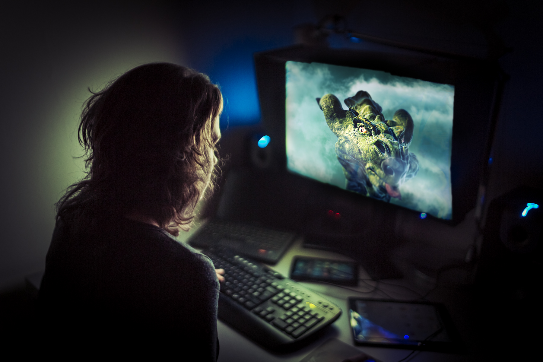 graphic artist working late at night. Dragon imagery is displayed on the monitor