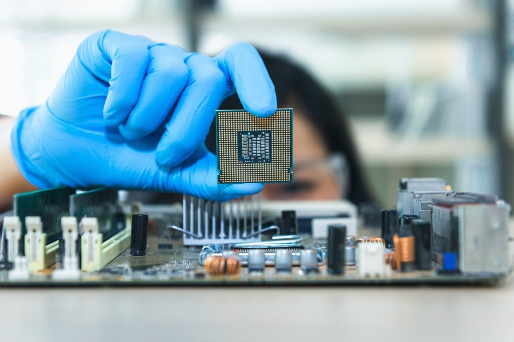 Close up portrait of a female computer engineer's hand holding up a CPU above a motherboard