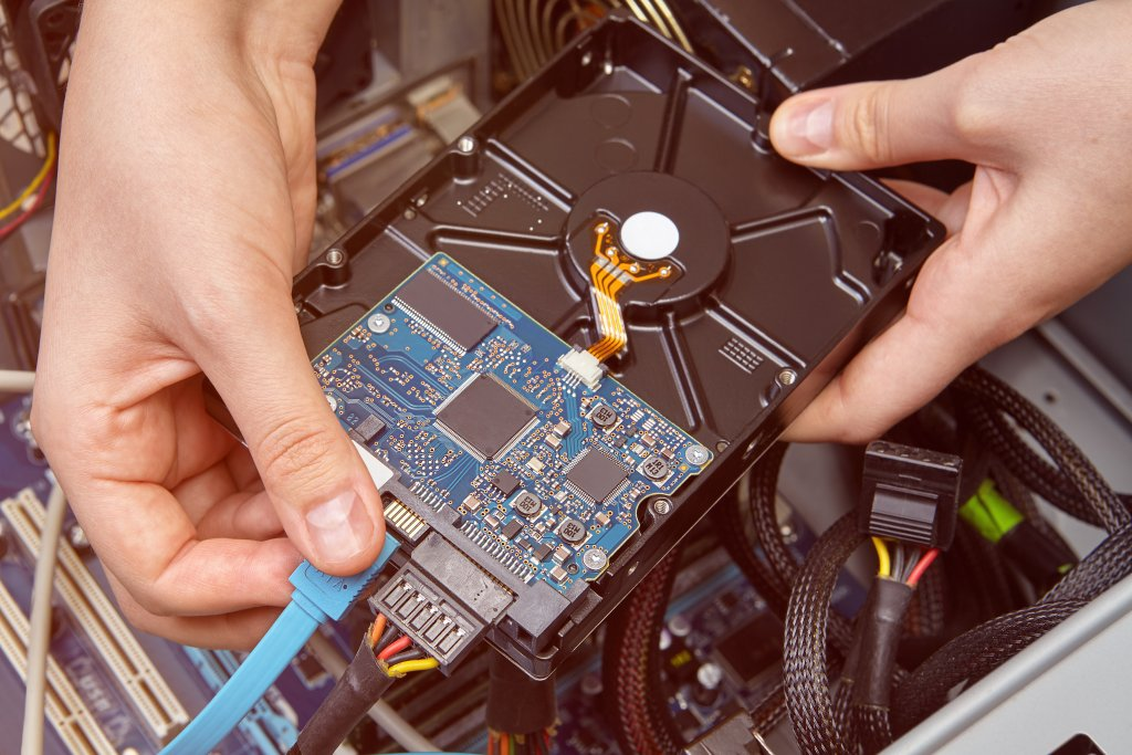 Repairman is connecting the SATA hard drive data cable to the personal computer.